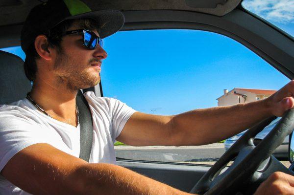 Uomo con occhiali da sole alla guida
